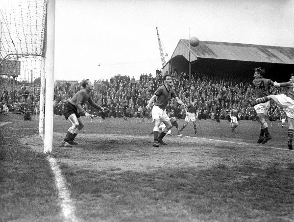 Plymouth Argyle's Harold Brown (l) and George Robertson (c) look on aghast as Millwall's Roy Summersby (far r) powers a header goalwards