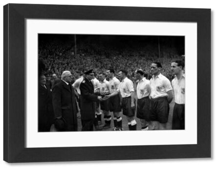 King George VI shakes hands with members of the Millwall team before kick off in this Wartime Cup Final