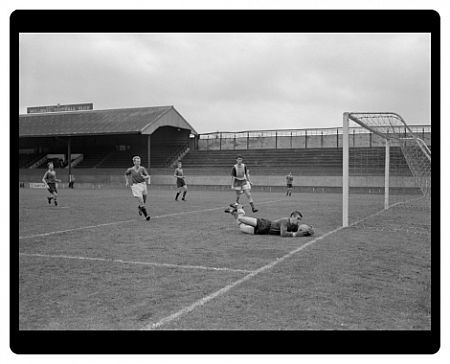 Goalkeeper Reg Davies dives and safely gathers the ball during the Trial match at The Den