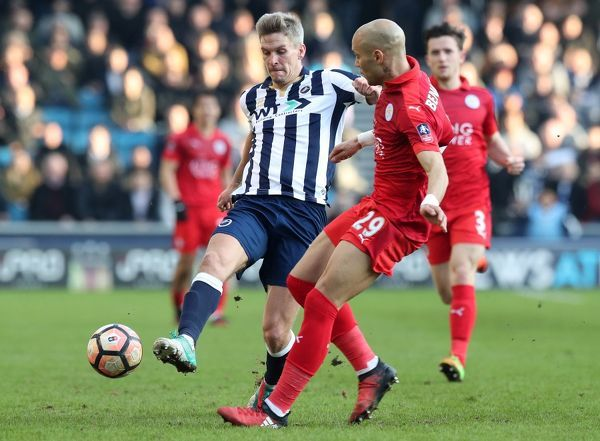 Millwall's Steve Morison and Leicester City's Yohan Benalouane (right) battle for the ball during the Emirates FA Cup, Fifth Round match at The Den, Millwall