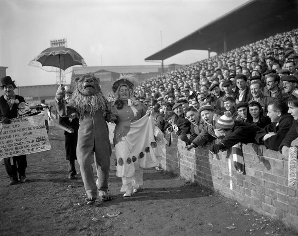 Rival supporters Ada Harwick, as a Gainsborough Lady from Birmingham, and Harry Ansell, as a Millwall Lion, parade long the touch line