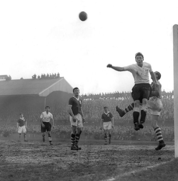 Birmingham City goalkeeper Gil Merrick winning a mid air duel with Millwall inside right John Shepherd and clears the ball with his fist
