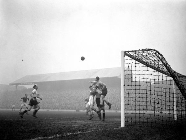 J. Varham, Tooting and Mitcham goalkeeper, clears the ball from James Constantine of Millwall
