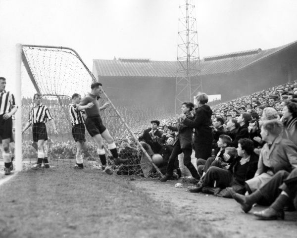 Newcastle United goalkeeper Ronnie Simpson almost joins the spectators as he goes to retrieve the ball behind his goal, where crowds packed to the edge of the pitch