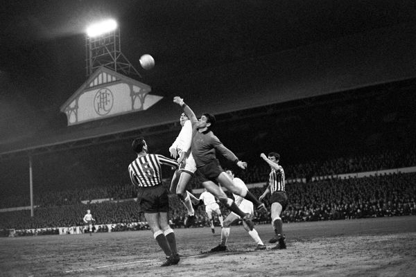 Millwall goalkeeper Lawrie Leslie leaps high to clear the ball from the head of Spurs' Alan Gilzean