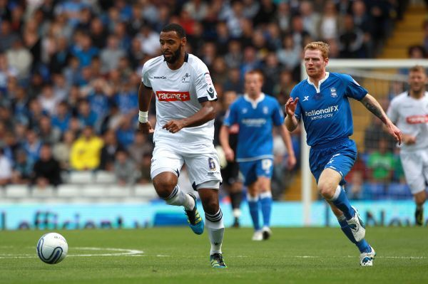 Birmingham City's Chris Burke chases down Millwall's Liam Trotter (left)