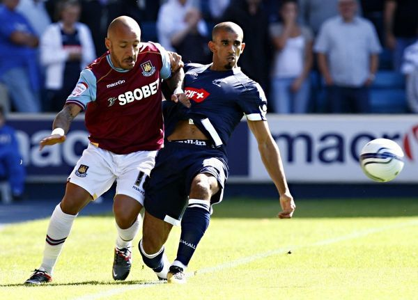 West Ham's Julien Faubert (left) in action with Millwall's Hamer Bouazza during the npower Football League Championship match at the Den, London