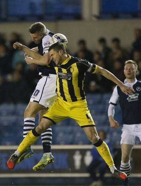 Millwall's Steve Morison and Burton Albion's John Mousinho battle for the ball during the Sky Bet League One match at the New Den, London