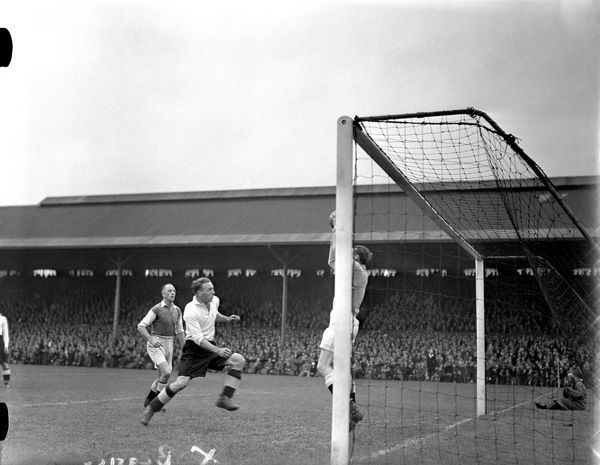 Millwall goalkeeper Jack Burke (r) claims the ball as Fulham's Pat Beasley (c) runs in to challenge