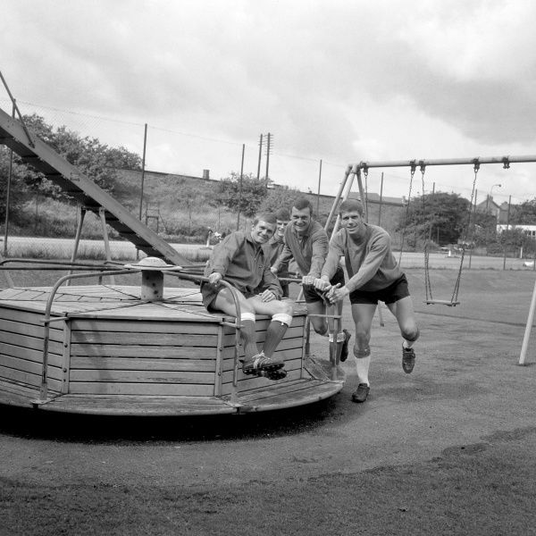 New Millwall signing Derek Possee is given a ride on a children's roundabout, near Millwall's practice pitch at Eltham, by his team-mates, (front to back), goalkeeper Lawrie Leslie, Keith Weller and forward William Neil
