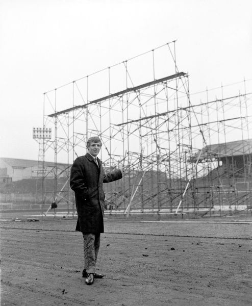 Millwall's new signing Eamonn Dunphy points to a huge television screen being constructed on the pitch at The Den to beam back pictures from Millwall's game at Workington on the 28th January Football League Division Three - Millwall